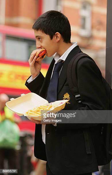 In this photo illustration school student Amir Shahin eats a burger and chips as part of his lunch which was brought from a fast food shop near his...