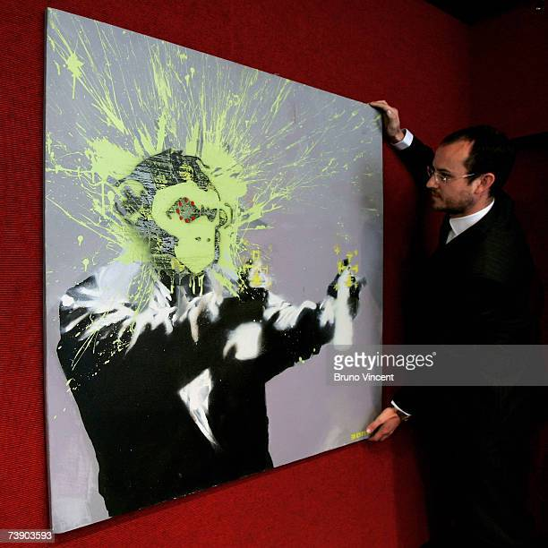 In this photo illustration specialist of 'Vision 21' Gareth Willams adjusts a selfportrait by Guerilla artist Banksy on April 17 2007 in London...