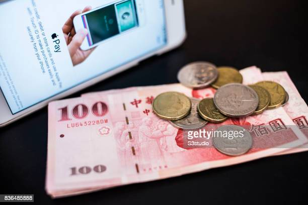 In this photo illustration Taiwanese New Taiwan dollar banknotes and Australian coins are placed next to the an iPhone with the Apple Pay application...