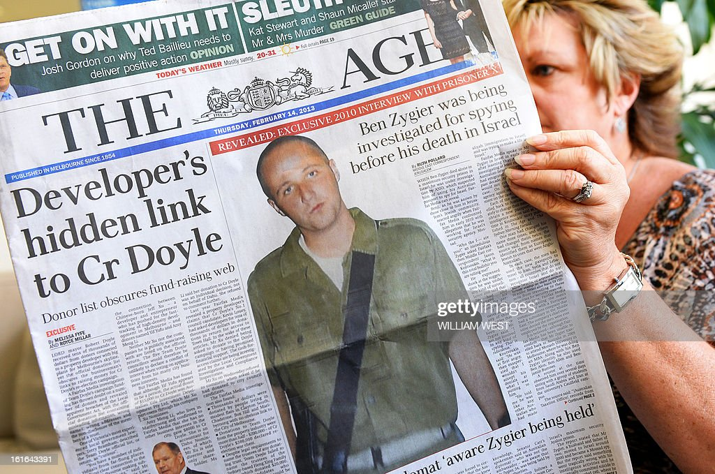 In this photo illustration taken in Sydney on February 14, 2013, a woman poses with an Australian newspaper showing the front page story of Ben Zygier, as Israel confirms it jailed a foreigner in solitary confinement on security grounds who later committed suicide, with Australia admitting it knew one of its citizens had been detained. The man, identified by Australian media as Mossad agent Ben Zygier, known as 'Prisoner X', died in a secret prison near Tel Aviv in 2010 in a case the Israeli government went to extreme lengths to cover up, imposing media gag orders. Tel Aviv broke its silence after the Australian Broadcasting Corporation said the man was a duel Australian-Israeli citizen and claimed he was a spy for Israel's intellegence agency. AFP PHOTO/William WEST