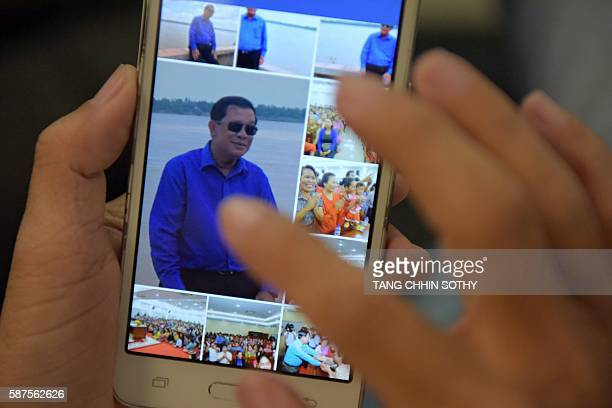 In this photo illustration taken on August 4 a Cambodian man in Phnom Penh browses through his smartphone displaying photos of Cambodian Prime...