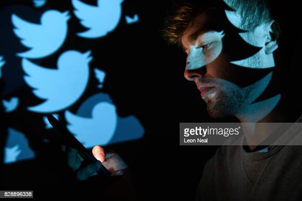 In this photo illustration the logo for the Twitter social media network is projected onto a man on August 09 2017 in London England With around 328...
