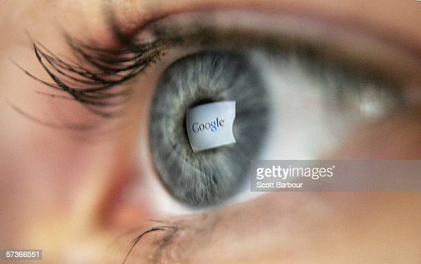 In this photo illustration the logo of the multifacetted internet giant Google is reflected in the eye of a woman looking at a computer screen April...