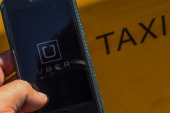 In this photo illustration the new smart phone app 'Uber' logo is displayed on a mobile phone next to a taxi on July 1 2014 in Barcelona Spain Taxi...