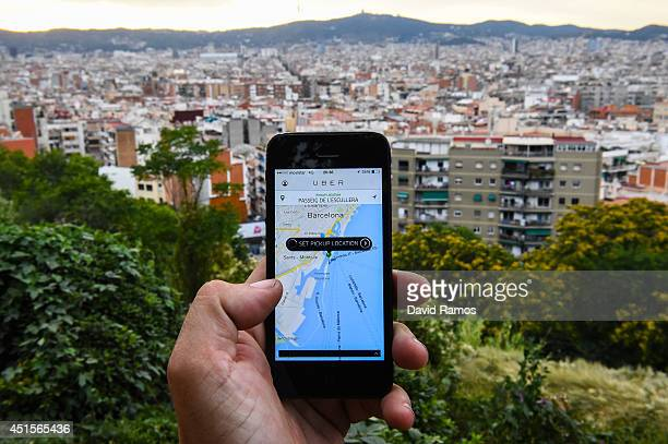 In this photo illustration the new smart phone taxi app 'Uber' shows how to select a pick up location backdropped by the skyline of Barcelona on July...