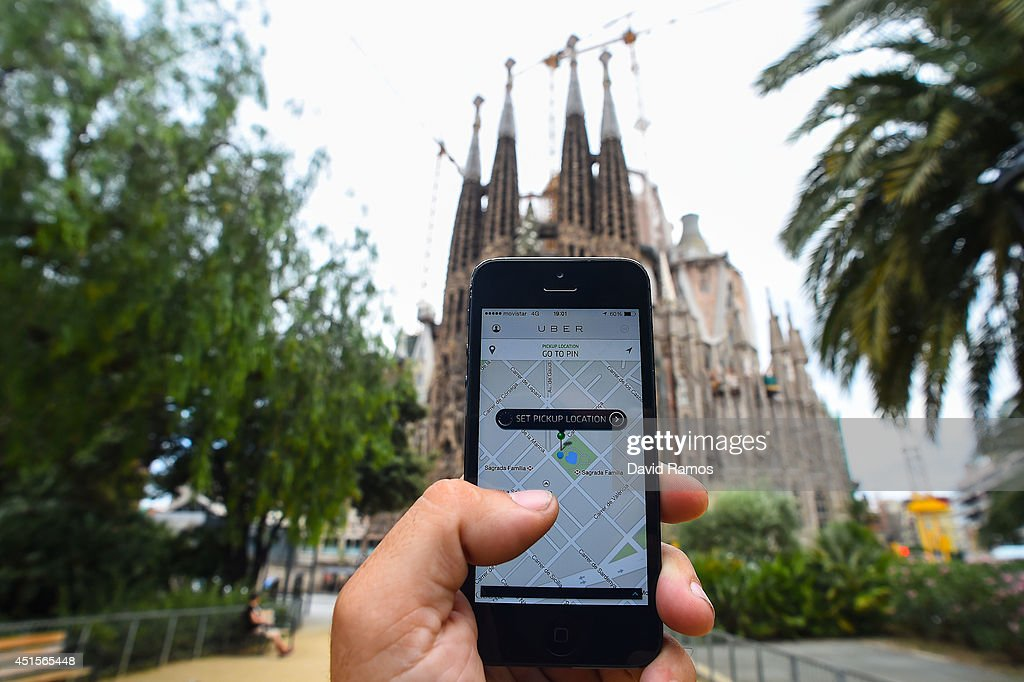 In this photo illustration the new smart phone taxi app 'Uber' shows how to select a pick up location backdropped by La Sagrada Familia on July 1, 2014 in Barcelona, Spain. Taxi drivers in various cities have been on strike over unlicensed car-hailing services. Drivers say that there is a lack of regulation behind the new app.