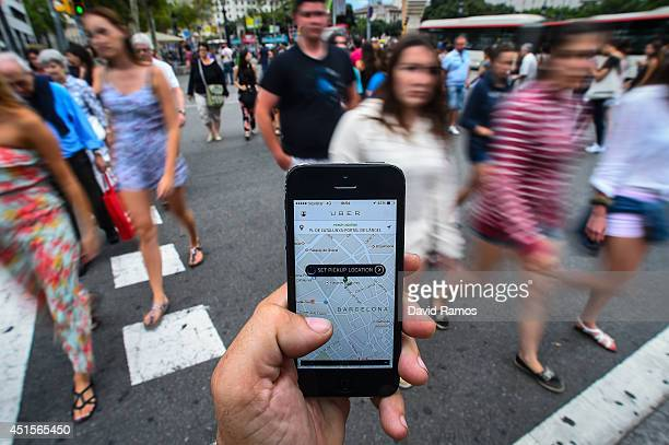 In this photo illustration the new smart phone taxi app 'Uber' shows how to select a pick up location at Plaza de Catalunya square on July 1 2014 in...