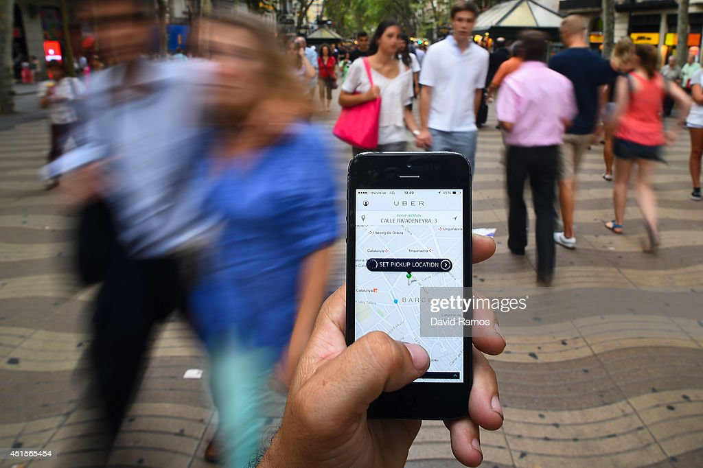 In this photo illustration the new smart phone taxi app 'Uber' shows how to select a pick up location in Las Ramblas street on July 1, 2014 in Barcelona, Spain. Taxi drivers in various cities have been on strike over unlicensed car-hailing services. Drivers say that there is a lack of regulation behind the new app.