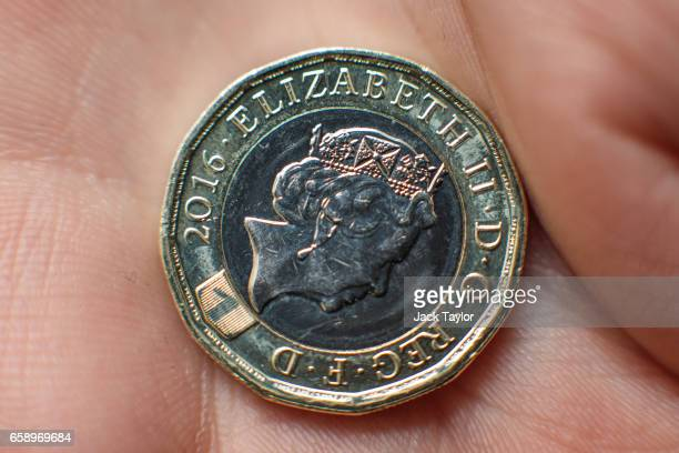 In this photo Illustration the newly issued £1 coin is held on March 28 2017 in London England The new £1 coin goes into circulation today and is...