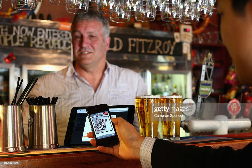 In this photo illustration, The Old Fitzroy Pub owner Garry Pasfield serves a customer using bitcoins on September 19, 2013 in Sydney, Australia. The Old Fitzroy pub in Sydney's eastern suburbs will accept the digital currency, Bitcoin, as of Next Sunday. Using a smartphone and a QR code scanning application customers will be able to purchase beer and menu items at the bar. The Old Fitzroy is the first Australian pub to accept Bitcoin payment.