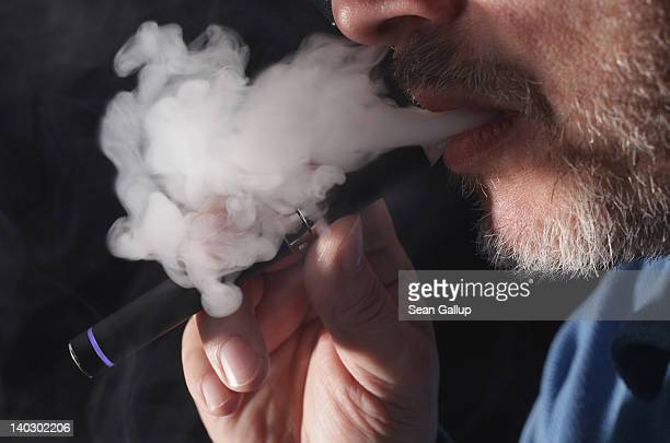 In this photo illustration the owner of a shop that sells electronic cigarettes demonstrates how to use one on March 1 2012 in Berlin Germany The...