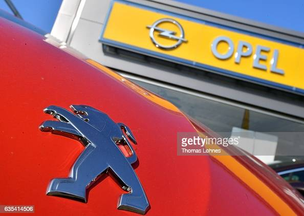In this photo illustration the Peugeot logo is seen on an engine hood and the Opel logo at a car dealer for Opel and Peugeut on February 15 2017 in...