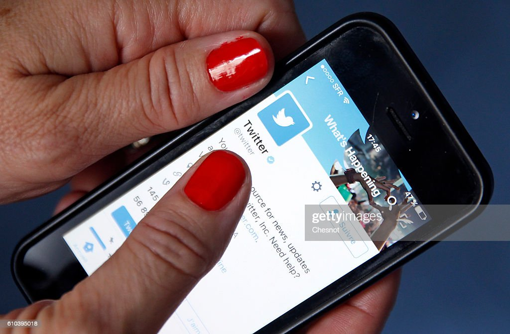 In this photo illustration, The social network Twitter home page is displayed on the screen of an Apple Inc. iPhone 5 in this arranged photograph on September 25, 2016 in Paris, France. According to information from the American television channel CNBC, the Twitter social network could be bought by Google (Alphabet) and Salesforce.com group before the end of the year.