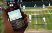 In this photo illustration the Twitter website is displayed on a mobile phone in front of a television showing the tennis at Wimbledon on July 2 2009...