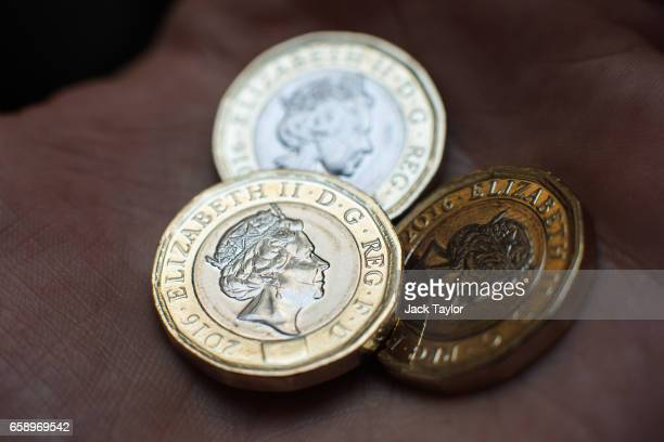In this photo Illustration three newly issued £1 coins are held on March 28 2017 in London England The new £1 coin goes into circulation today and is...