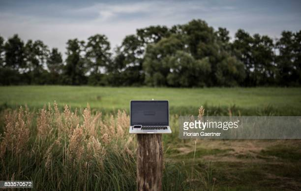 In this photo illustration to the topic 'Internet access in rural areas' a laptop and a smartphone on a wooden pillar are pictured on August 15 2017...