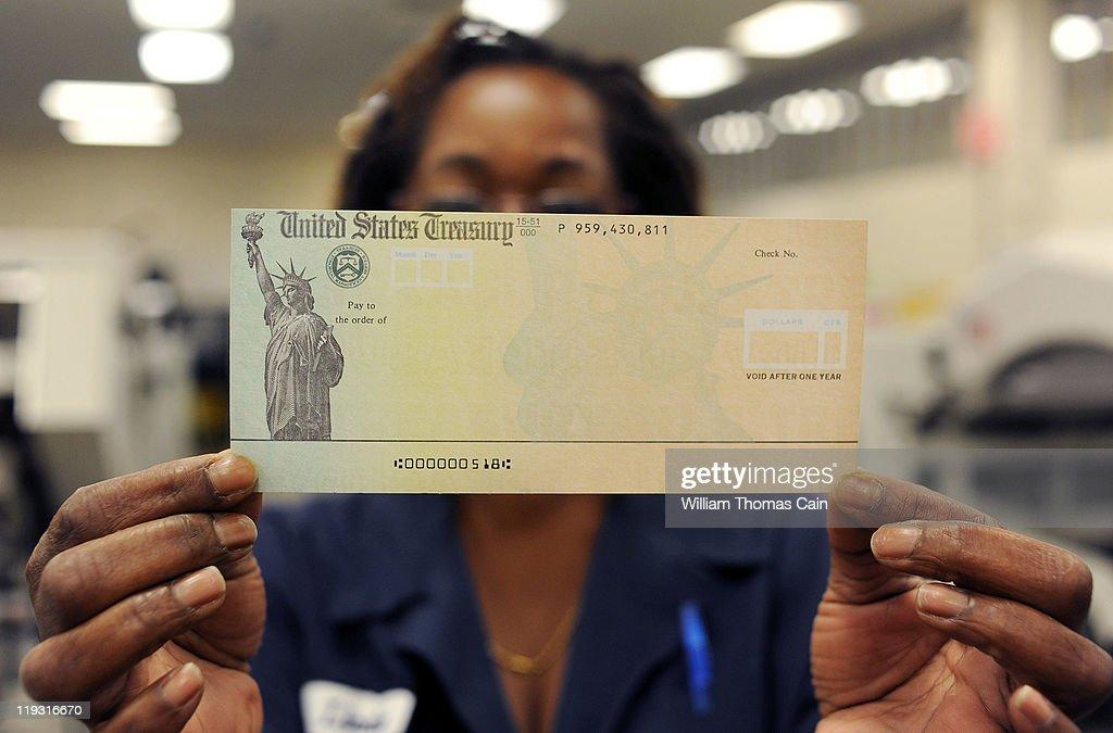 In this photo illustration Treasury employee Linda Tarkenton of Philadelphia Pennsylvania holds a blank US Treasury check before it's run through a...