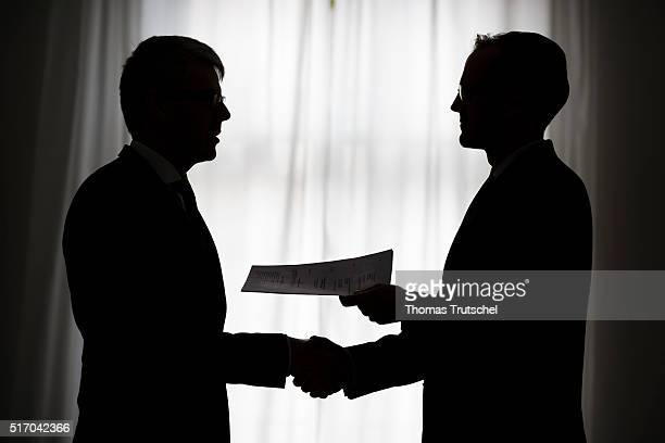 In this Photo Illustration two men shake hands and hold a contract in the hands on March 23 2016 in Berlin Germany