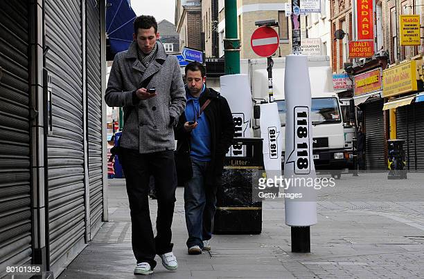In this photo illustration two pedestrians walks past padded lamp posts whilst texting in Brick Lane on March 4 2008 in London England Brick Lane has...
