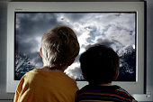 In this photo illustration two young child watch television at home January 27 2005 in London England