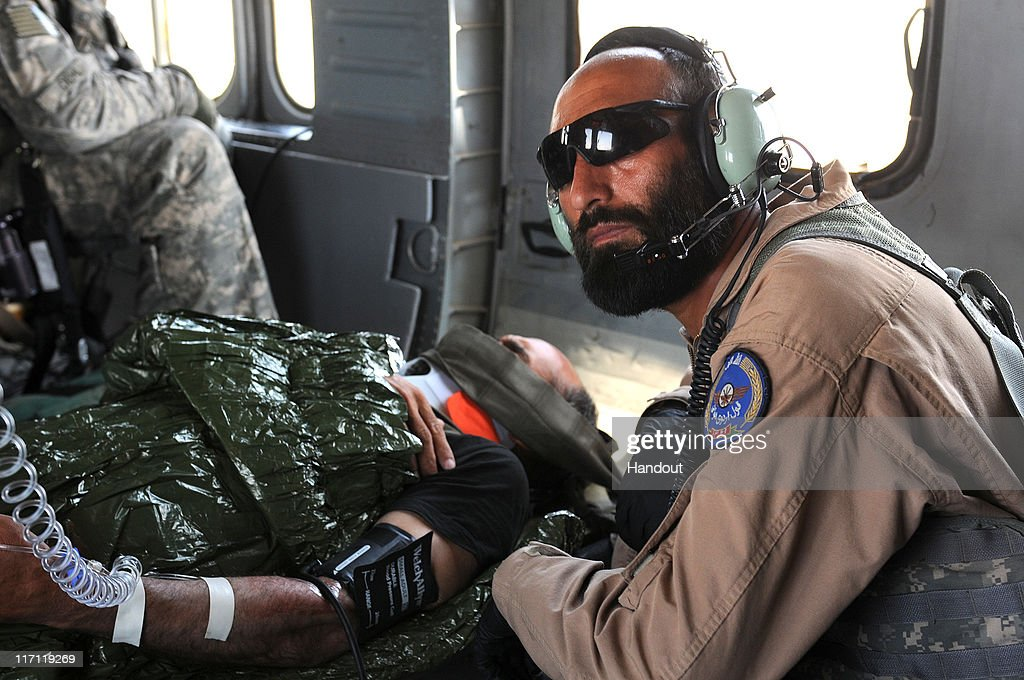 In this photo provided by ISAF Regional Command (South), Afghan Air Force flight medic Sgt. Gulap Ahmadzia monitors the blood pressure and pulse of an Afghan National Army soldier during a medical evacuation to the Afghan National Army hospital on June 22, 2011, at Camp Hero, Kandahar, Afghanistan. Ahmadzia is the first Afghan flight medic to join American medevac crews as they evacuate more serious patients from the battlefield. The Afghan medics will continue to work with the American teams on a regular basis, gradually increasing the severity of the patients they treat.