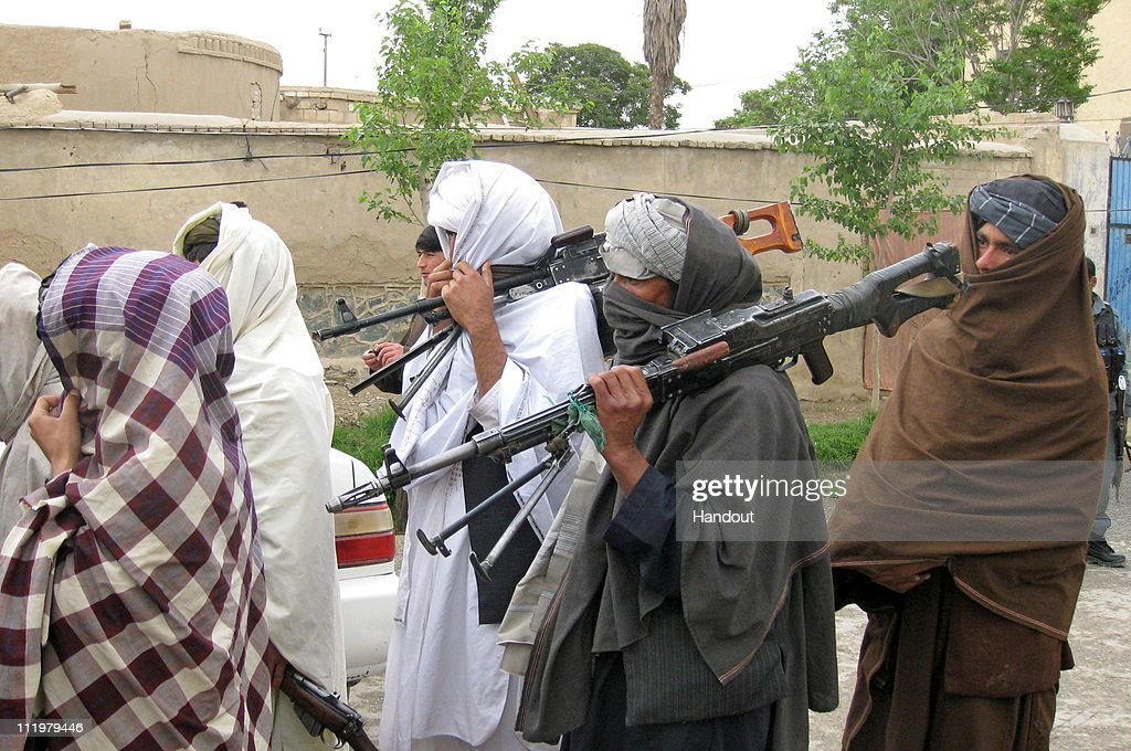 In this photo provided by ISAF Regional Command Taliban fighters peacefully surrender their arms during a meeting with Afghan government officials as...