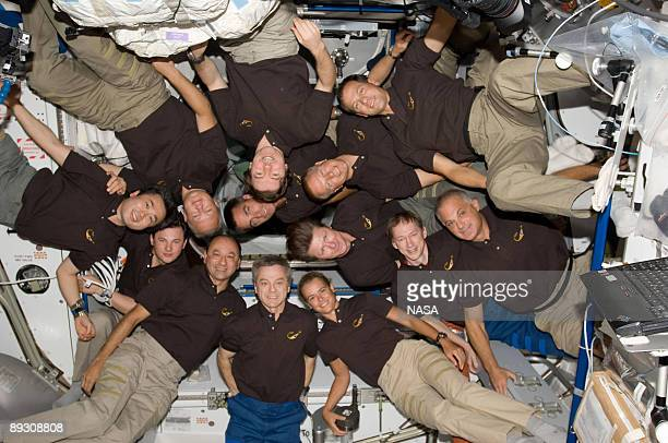 In this photo provided by NASA A record 13 astronauts and cosmonauts assemble for a shuttlestation group photo on the orbiting outpost July 25 2009...