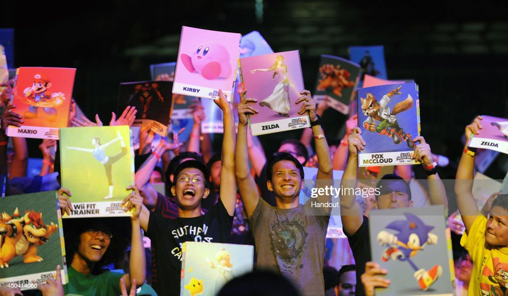 In this photo provided by Nintendo of America, audience members cheer for their fan favorite contestant to move on to the next round of the Super Smash Bros. Invitational tournament at NOKIA Theatre L.A. LIVE on June 10, 2014 in Los Angeles, California.