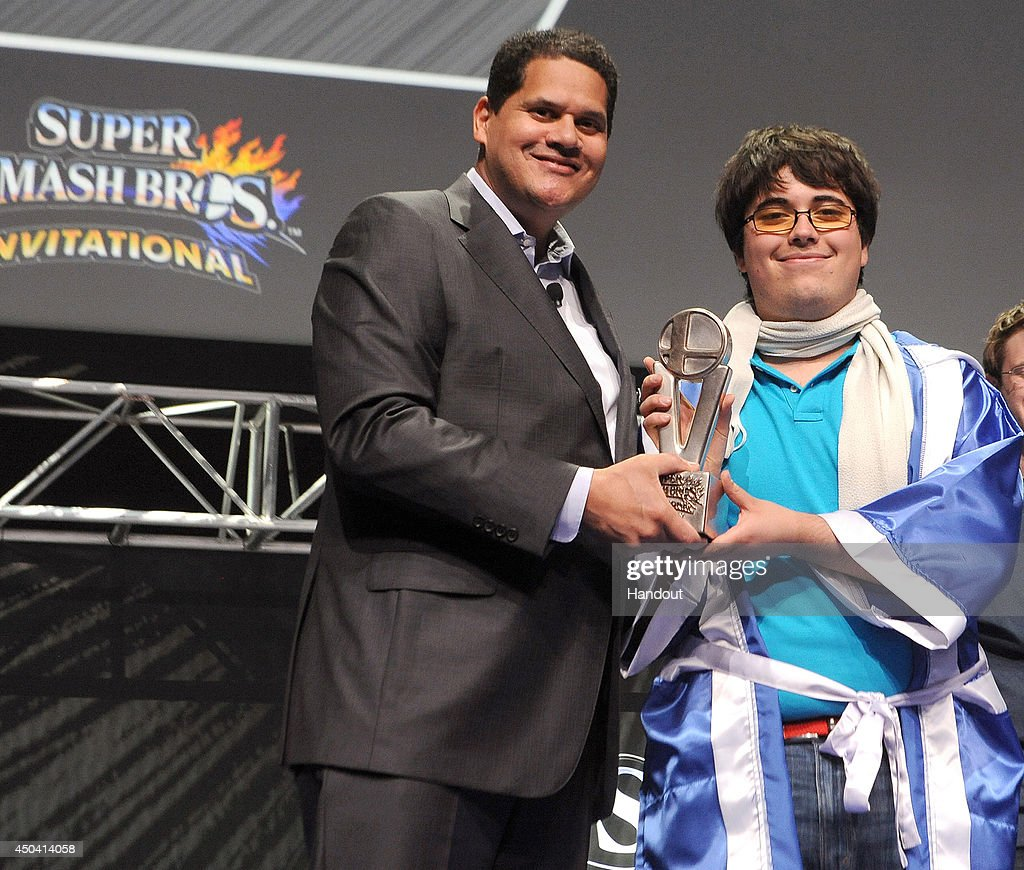 In this photo provided by Nintendo of America, Super Smash Bros. Invitational winner Gonzalo 'ZeRo' Barrios of Chillan, Chile receives the grand-prize trophy from Nintendo of America President and COO Reggie Fils-Aime as winner of the Super Smash Bros. Invitational on June 10, 2014 in Los Angeles, California. Thousands of fans in the audience and countless more watching online celebrated the Super Smash Bros. franchise in anticipation of the game's launch this year on both Nintendo 3DS and Wii U.