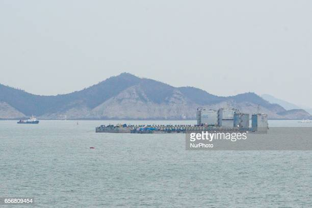 In this photo provided by South Korean Maritime Ministry two barges attempt to salvage the sunken Sewol ferry in waters off Jindo South Korea...