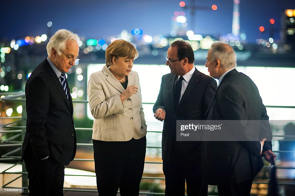 In this photo provided by the German Government Pres Office (BPA), German Chancellor <a gi-track='captionPersonalityLinkClicked' href=/galleries/search?phrase=Angela+Merkel&family=editorial&specificpeople=202161 ng-click='$event.stopPropagation()'>Angela Merkel</a> speaks with new French President Francois Hollande next to two translators before a working dinner at the Chancellery hours after Hollande's inauguration in Paris on May 15, 2012 in Berlin, Germany. Hollande has come to Berlin to discuss the current European debt crisis with Merkel and most importantly to find common ground, as he hopes to resolve the crisis with measures that mark a departure from the austerity packages favoured by Merkel.