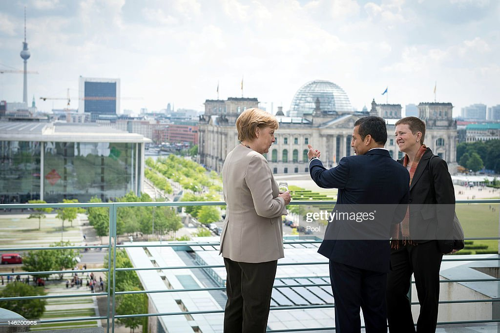 In this photo provided by the German Government Press Office (BPA), Chancellor <a gi-track='captionPersonalityLinkClicked' href=/galleries/search?phrase=Angela+Merkel&family=editorial&specificpeople=202161 ng-click='$event.stopPropagation()'>Angela Merkel</a> talks (L) talks with Peruvian President <a gi-track='captionPersonalityLinkClicked' href=/galleries/search?phrase=Ollanta+Humala&family=editorial&specificpeople=588227 ng-click='$event.stopPropagation()'>Ollanta Humala</a> Tasso with help of an interpreter (R) on the rooftop terrace of the Chancellery on June 12, 2012 in Berlin, Germany.