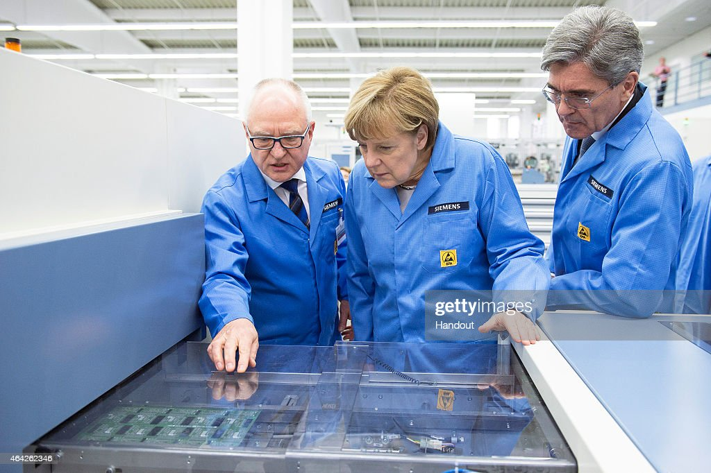 In this photo provided by the German Government Press Office (BPA), Professor Karl-Heinz Büttner (L), head of the Siemens plant in Amberg and <a gi-track='captionPersonalityLinkClicked' href=/galleries/search?phrase=Joe+Kaeser&family=editorial&specificpeople=558326 ng-click='$event.stopPropagation()'>Joe Kaeser</a> (R), CEO of Siemens talk German Chancellor <a gi-track='captionPersonalityLinkClicked' href=/galleries/search?phrase=Angela+Merkel&family=editorial&specificpeople=202161 ng-click='$event.stopPropagation()'>Angela Merkel</a> through the process of printing a circuit board during her visit to the Siemens AG Electronics Manufacturing Plant on February 23, 2015 in Amberg, Germany. The Chancellor visited the Siemens AG Electronics Manufacturing Plant to witness the digitization of the industry. In a speech after the visit she concluded that 'Germany is not rich in natural resources but rich in ideas'.