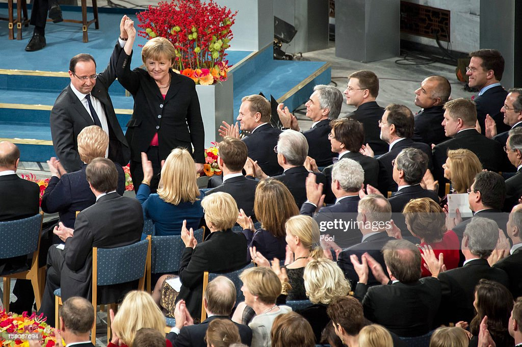 In this photo provided by the German Government Press Office (BPA), EU leaders applaud as German Chancellor Angela Merkel raises her hand with French President Francois Hollande during the Nobel Peace Prize Ceremony at Oslo City Hall on December 10, 2012 in Oslo, Norway. The European Union has collected this year's prestigious Nobel Peace Prize for uniting the continent after two World Wars.