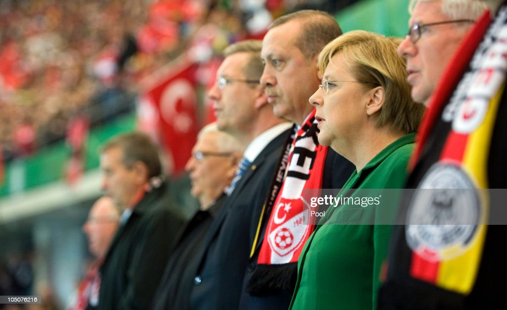 In this photo provided by the German Government Press Office, German Chancellor <a gi-track='captionPersonalityLinkClicked' href=/galleries/search?phrase=Angela+Merkel&family=editorial&specificpeople=202161 ng-click='$event.stopPropagation()'>Angela Merkel</a>, Turkish Prime Minister Recep Erdogan, German President <a gi-track='captionPersonalityLinkClicked' href=/galleries/search?phrase=Christian+Wulff&family=editorial&specificpeople=221618 ng-click='$event.stopPropagation()'>Christian Wulff</a>, and DFB President <a gi-track='captionPersonalityLinkClicked' href=/galleries/search?phrase=Theo+Zwanziger&family=editorial&specificpeople=206980 ng-click='$event.stopPropagation()'>Theo Zwanziger</a> (R-L) sing the German anthem prior to the EURO 2012 group A qualifier match between Germany and Turkey at the Olympic Stadium on October 8, 2010 in Berlin, Germany.