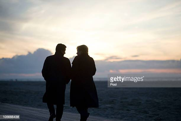 In this photo provided by the German Government Press Office German Chancellor Angela Merkel walks together with French President Nicolas Sarkozy at...