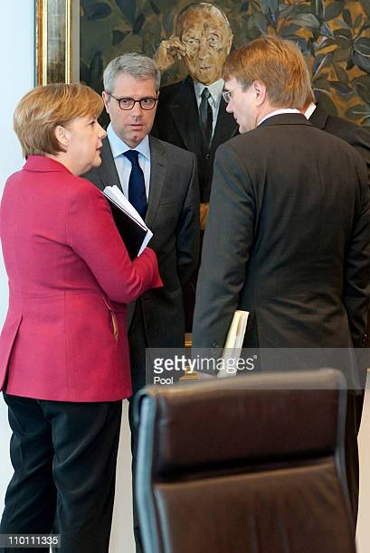 In this photo provided by the German Government Press Office German Chancellor Angela Merkel speaks to German Environment Minister Nobert Roettgen...