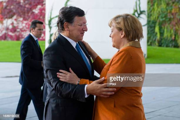 In this photo provided by the German Government Press Office German Chancellor Angela Merkel greets President of the European Commission Jose Manuel...