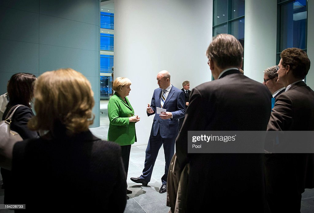 In this photo provided by the German Government Press Office (BPA) German Chancellor Angela Merkel and Swedish Prime Minister Fredrik Reinfeldt speak with their employees at the start of their meeting at the Chancellery on October 16, 2012 in in Berlin, Germany.
