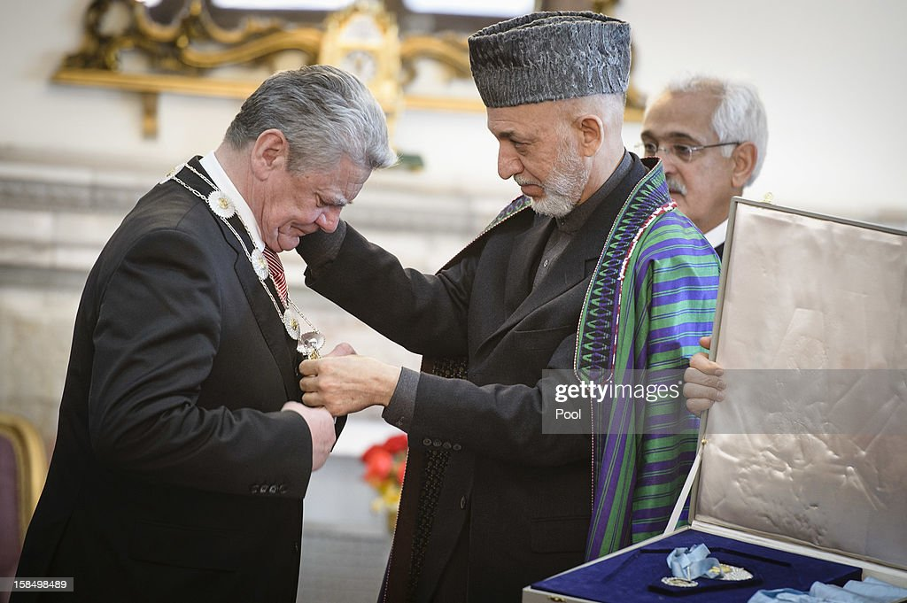In this photo provided by the German Government Press Office (BPA), German President <a gi-track='captionPersonalityLinkClicked' href=/galleries/search?phrase=Joachim+Gauck&family=editorial&specificpeople=2077888 ng-click='$event.stopPropagation()'>Joachim Gauck</a> receives the Order of the Sun by Afghan President <a gi-track='captionPersonalityLinkClicked' href=/galleries/search?phrase=Hamid+Karzai&family=editorial&specificpeople=121540 ng-click='$event.stopPropagation()'>Hamid Karzai</a> at the Presidential Palace on December 18, 2012 in Kabul, Afghanistan. The visit is Gauck's first to the region since taking office.