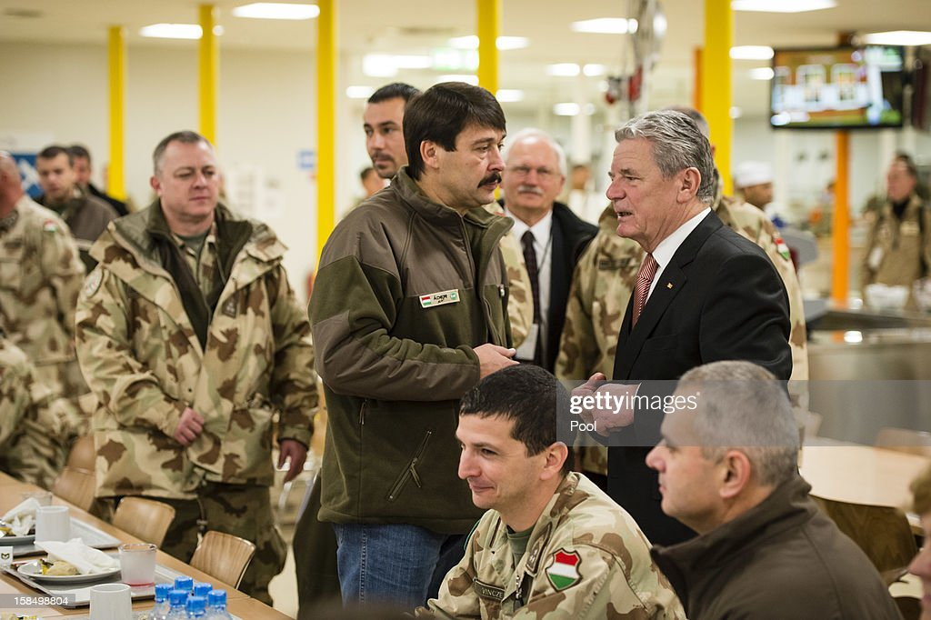 In this photo provided by the German Government Press Office (BPA), German President Joachim Gauck (R) talks to Hungarian President Janos Ader (C) after having breakfast in the canteen at Camp Marmal on December 18, 2012 in Masar-i-Scharif in Afghanistan. The visit is Gauck's first to the region since taking office.