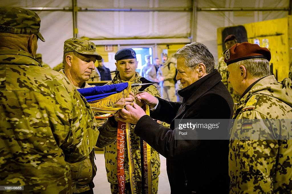 In this photo provided by the German Government Press Office (BPA), German President Joachim Gauck attachs bands to the flag of the U.S. 158th Aviation Regiment, whose Battalion is located in Kattelbach Germany, at Camp Marmal on December 19, 2012 in Mazar-i-Sharif, Afghanistan. The visit is Gauck's first to the region since taking office during which he has held talks with Afghan president Hamid Karzai and government representatives.