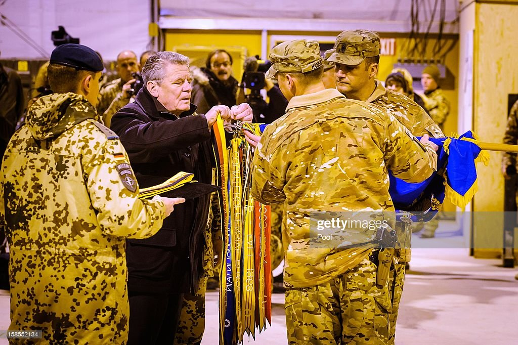 In this photo provided by the German Government Press Office (BPA), German President Joachim Gauck attachs bands to the flag of the U.S. 1st Battalion, 211th Aviation Regiment stationed at Camp Marmal on December 19, 2012 in Mazar-i-Sharif, Afghanistan. The visit is Gauck's first to the region since taking office during which he has shown his support for German troops stationed there and also held talks with Afghan president Hamid Karzai and government representatives in Kabul.