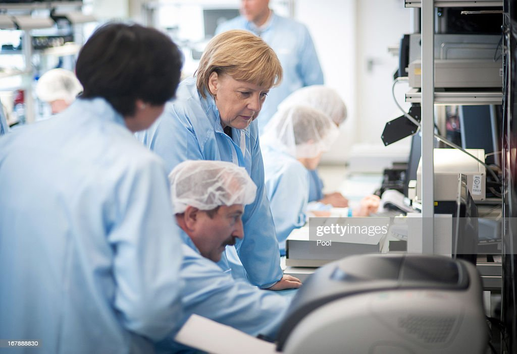 In this photo provided by the German Government Press Office (BPA), German Chancellor <a gi-track='captionPersonalityLinkClicked' href=/galleries/search?phrase=Angela+Merkel&family=editorial&specificpeople=202161 ng-click='$event.stopPropagation()'>Angela Merkel</a> wears overalls as she visits Jena-Optronik GmbH (Ltd) factory on May 2 , 2013 in Jena, eastern Germany. Merkle's visit comes a day after the Christian Democrats dropped to their lowest level in the pools following a tax evasion case involving a prominent party ally.