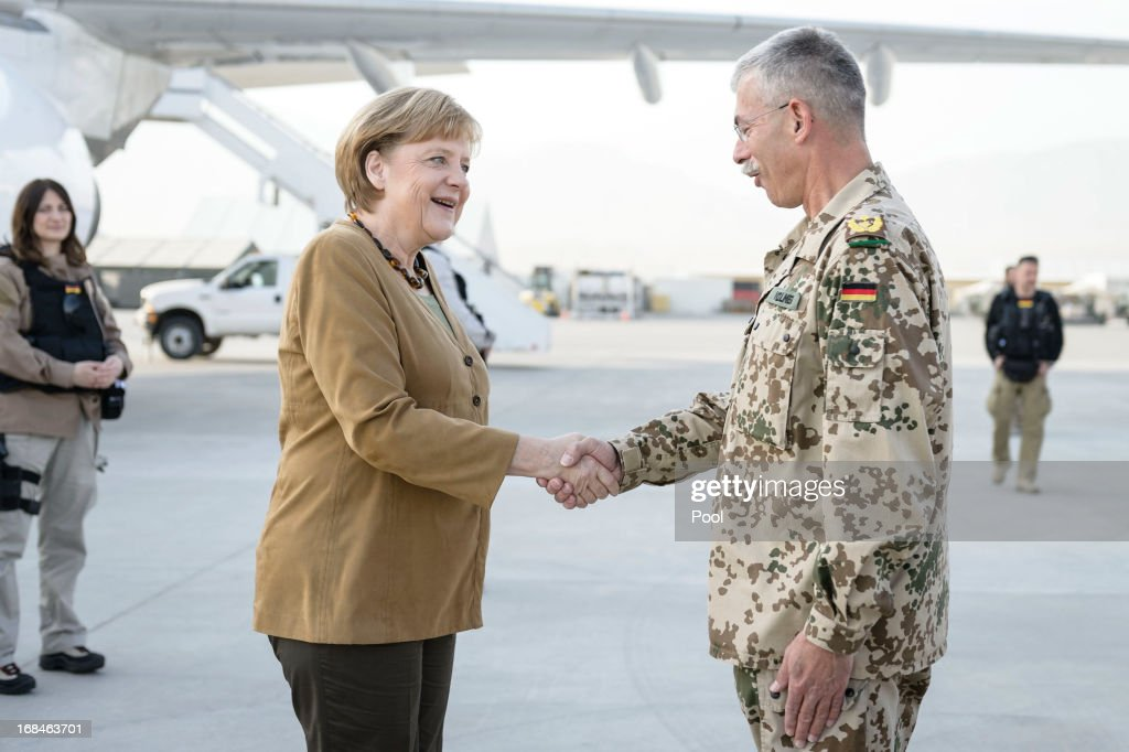 In this photo provided by the German Government Press Office (BPA), German Chancellor <a gi-track='captionPersonalityLinkClicked' href=/galleries/search?phrase=Angela+Merkel&family=editorial&specificpeople=202161 ng-click='$event.stopPropagation()'>Angela Merkel</a> greets ISAF Regional Commander North German general Joerg Vollmer as she arrives at the German's troop base Camp Marmal on May 10, 2013 in Mazar-i-Sharif, Afghanistan. Merkel visited German soldiers currently deployed and paid her respects to those who lost their lives during the conflict. She is being accompanied by Defense Minister Thomas de Maizière.
