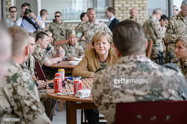 In this photo provided by the German Government Press Office German Chancellor Angela Merkel talks to soldiers in a mess hall on May 10 2013 in...