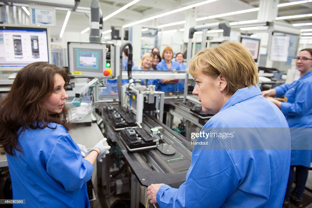 In this photo provided by the German Government Press Office German Chancellor Angela Merkel speaks to a member of staff about the collaboration...