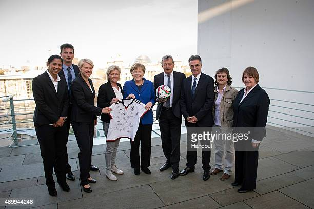 In this photo provided by the German Government Press Office German Chancellor Angela Merkel holds a shirt with DFB President Wolfgang Niersbach and...
