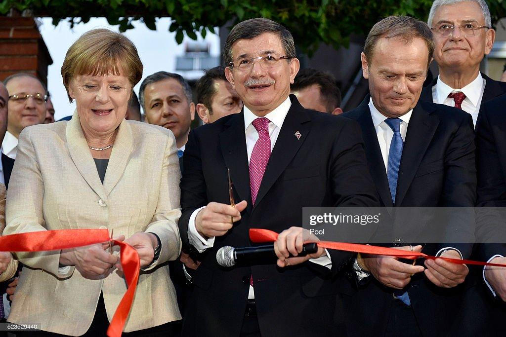 In this photo provided by the German Government Press Office (BPA), German Chancellor Angela Merkel, Turkey's Prime Minister Ahmet Davutoglu and President of the European Council Donald Tusk cuts a red ribbon opening a child protection center on April 23, 2016 in Gaziantep, Turkey. Merkel is in Germany to commence the EU aid program for Syrians in Turkey and visit a refugee camp.