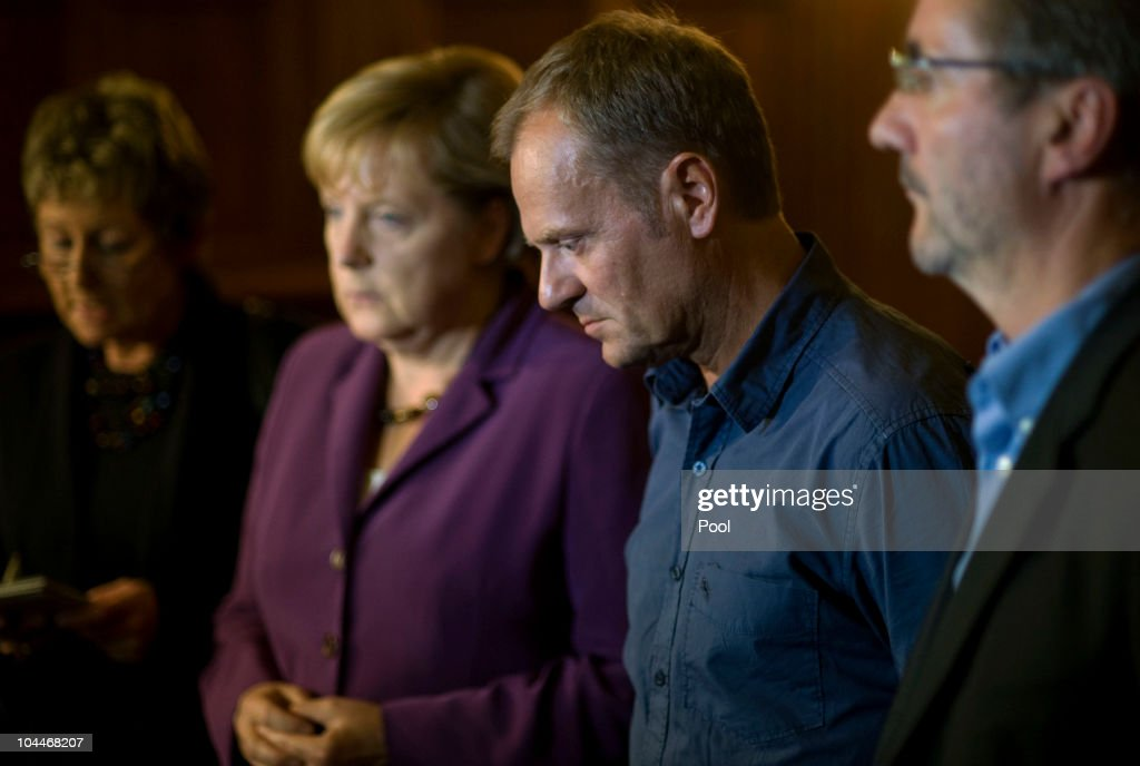 In this photo provided by the German Government Press Office, Polish Prime Minister <a gi-track='captionPersonalityLinkClicked' href=/galleries/search?phrase=Donald+Tusk&family=editorial&specificpeople=870281 ng-click='$event.stopPropagation()'>Donald Tusk</a> (C) gives a statement to the bus accident next to German Chancellor <a gi-track='captionPersonalityLinkClicked' href=/galleries/search?phrase=Angela+Merkel&family=editorial&specificpeople=202161 ng-click='$event.stopPropagation()'>Angela Merkel</a> at the Polish embassy on September 26, 2010 in Berlin, Germany. Tusk came to Germany after a polish bus crashed on the A10 highway and 13 persons died. The bus was carrying forest workers who came back from a company trip to Spain.